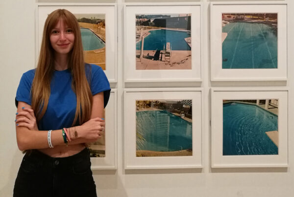 Cristina Ricci in front of Ed Ruscha's photographs of nine swimming pools