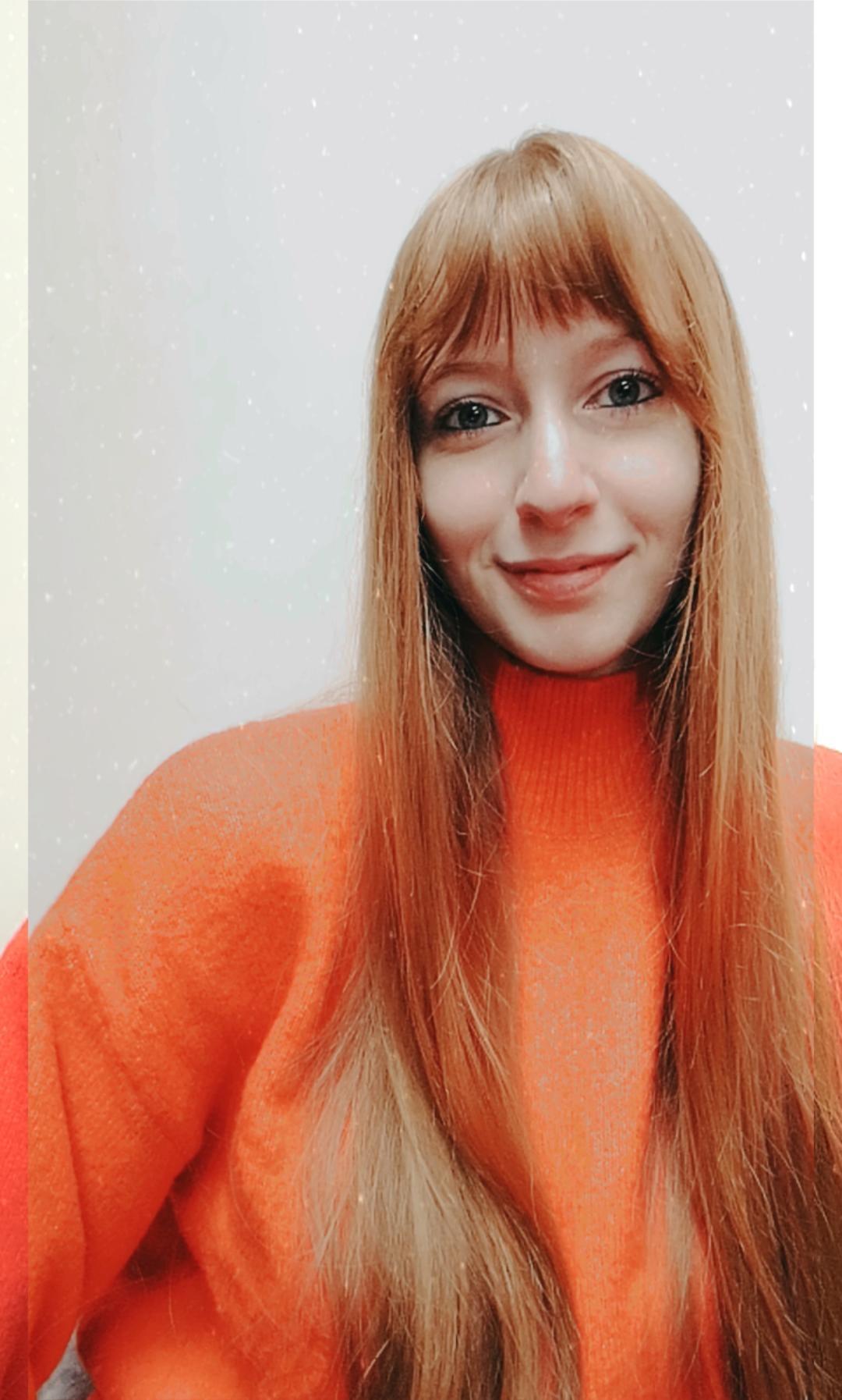 Cristina Ricci wearing an orange jumper