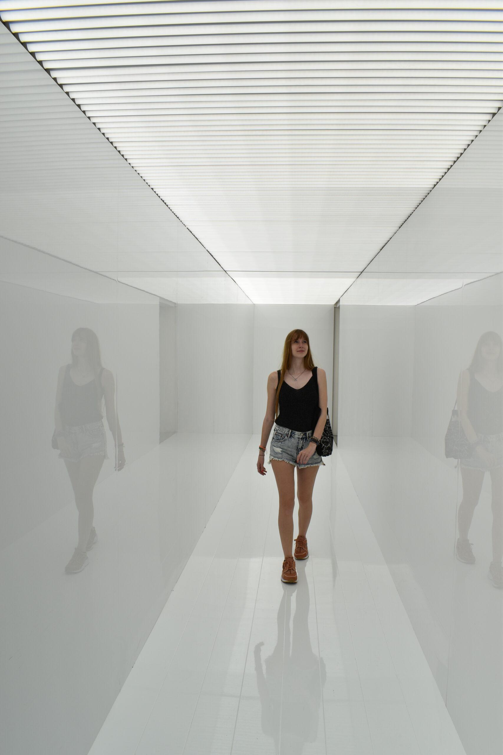Cristina walking through a corridor of bright light